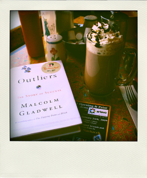 Polaroid of Malcolm Gladwell's Outliers and a hot chocolate